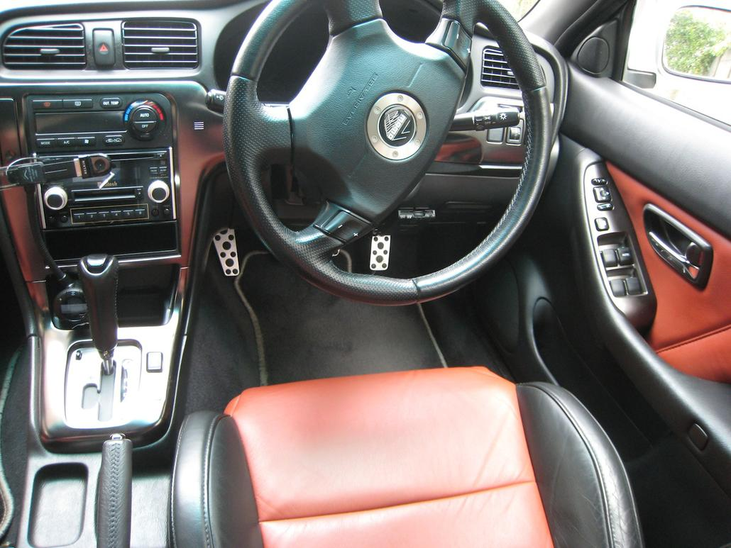 Interior view of car with Momo steering wheel and nice pedals.